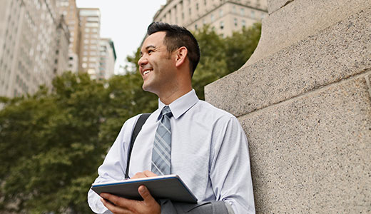A businessman smiling and using a tablet